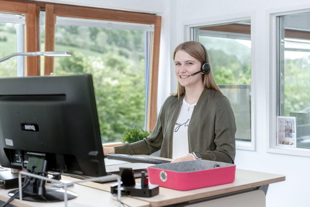 Junge Frau sitzt lächelnd mit einem Headset am Computer Bildschirm und arbeitet